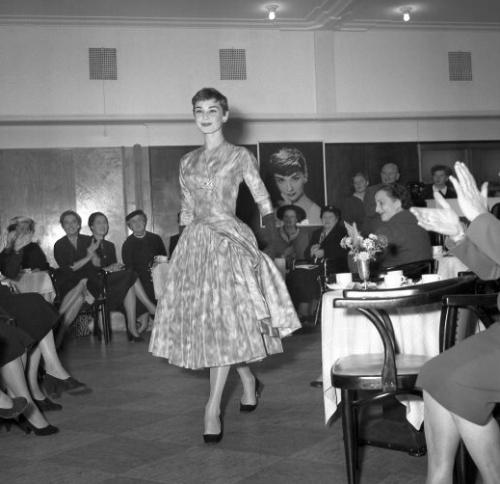 L'actrice Audrey Hepburn présente une création du couturier Hubert de Givenchy, lors d'un défilé de mode, en novembre 1954, à Amsterdam. Actress Audrey Hepburn shows a Givenchy model, during a fashion show, in November 1954, in Amsterdam.